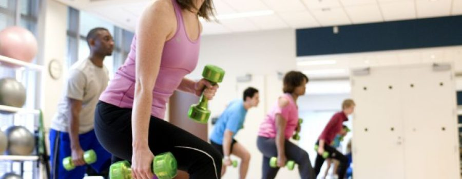 People in a gym doing exercises with dumbbells