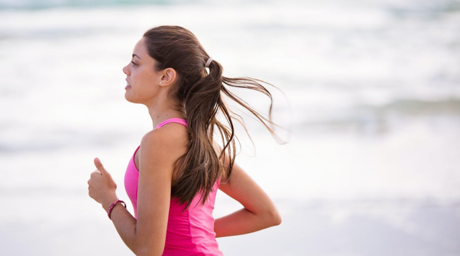 A woman jogging in a pink shirt at the beach